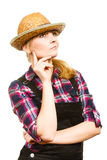 Thinking woman wearing sun hat and dungarees Royalty Free Stock Images