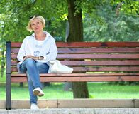 Thinking Woman in White Jacket and White Scoop Neck Shirt Blue Denim Jeans Sitting on Brown Wooden Bench Beside Green Trees during stock photos