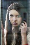 The thinking woman at window stock photography