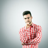 Thinking worried young man in plaid shirt Stock Images