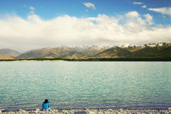 Thinking of You. An Asian woman sitting in front of a Lake, enjoying beautiful view of New Zealand mountains Royalty Free Stock Images