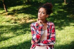 Thinking young african woman sitting outdoors in park. Photo of serious thinking young african woman sitting outdoors in park. Looking camera royalty free stock photos