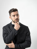 Thinking young bearded man in tuxedo with bow tie touching beard looking away. Royalty Free Stock Image