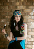 Thinking young beautiful hippie girl in headscarf. Young beautiful black-haired bohemian-styled girl holding feather and looking sideways on brick wall royalty free stock image