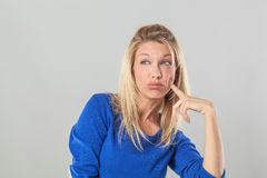 Thinking young blond woman looking away with index on cheek Stock Image