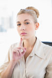 Thinking young blonde businesswoman looking at camera Royalty Free Stock Photo