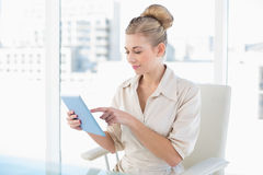 Thinking young blonde businesswoman using a tablet pc Stock Photography