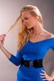 Thinking young blonde girl examining hair Stock Photo