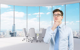 Thinking young businessman. Standing in modern office Stock Images