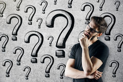 Thinking man with question marks. Thinking young caucasian man standing on concrete wall background with question marks. Curious, confusion, faq concept Stock Photos