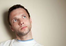 Thinking young Caucasian man in white t-shirt Royalty Free Stock Image
