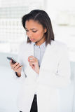 Thinking young dark haired businesswoman looking at her mobile phone Royalty Free Stock Photography