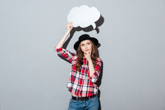 Thinking young lady holding speech bubble. Royalty Free Stock Photography