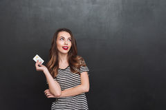 Thinking young lady standing over grey wall holding debit card. Picture of thinking young lady standing over grey wall and holding debit card in hands. Looking stock photos