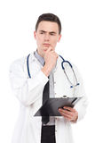 Thinking young male doctor with a clipboard Stock Photos