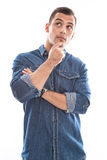 Thinking: young man in blue denim shirt isolated on white backgr Stock Image