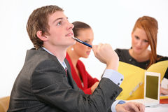 Thinking young man with colleagues Royalty Free Stock Photography