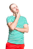 Thinking young man in striped white and turquoise t-shirt and orange jeans isolated on white Royalty Free Stock Images