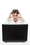 Thinking young office worker with laptop isolated Stock Images