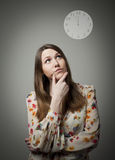 Thinking. Young woman and clock. Stock Photography