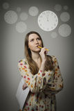 Thinking. Young woman and clock. Stock Photos