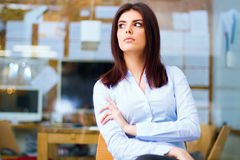 Thinking young woman looking away in office. Portrait of a thinking young woman looking away in office Royalty Free Stock Images