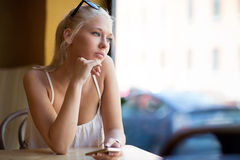 Thinking young woman looking out the window Royalty Free Stock Images