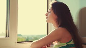 Thinking young woman looking from window and enjoying air stock footage