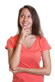 Thinking young woman in a red shirt Stock Image