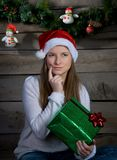 Thinking Young Woman In Santa Hat With Christmas Gift. New Year. Stock Images