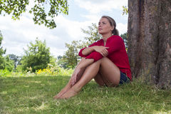 Thinking young woman sitting under a tree for summer freshness Stock Photography