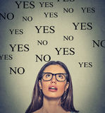 Thinking young woman with yes or no choice looking up. On grey wall background Royalty Free Stock Photography