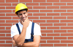 Thinking young worker in front of a brick wall Stock Image
