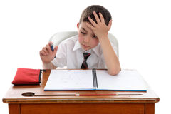 Thinkinhg del muchacho en el escritorio de la escuela imagen de archivo libre de regalías