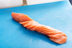 Thinly sliced fillet of fresh raw salmon. Cut on the diagonal for use as an ingredient in sushi and sashimi lying on a blue cutting board with copy space Royalty Free Stock Image