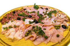 Thinly sliced ham and  salami with greens. Royalty Free Stock Images