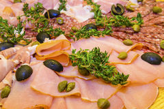 Thinly sliced ham and  salami with greens. Thinly sliced ham and  salami with olives, capers and  fresh thyme   on wooden background Stock Photography