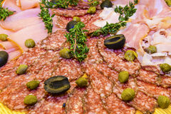 Thinly sliced ham and  salami with greens. Thinly sliced ham and  salami with olives, capers and  fresh thyme   on wooden background Stock Photos