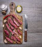 Thinly sliced lamb with garlic on a cutting board with a knife for meat, butter and salt border ,text area on wooden rustic b Stock Photos