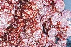 Thinly sliced sausage slices on a black stone board. stock image