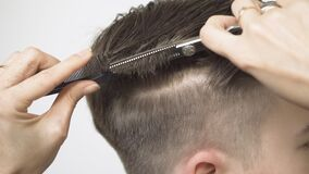Thinning hair on the temporal area with thinning scissors close-up.