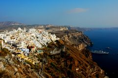 Thira (Fira) in Santorini, Greece. An overview of the cliffside town of Thira (Fira) in Santorini, Greece. The cliff is dotted by numerous Grecian houses and Stock Photography