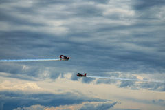 Third AirFestival at Chaika airfield. Two small red aircraft are flying towards. Thunderclouds at the background. Royalty Free Stock Photo