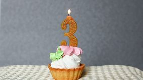 Third anniversary, happy birthday cake with number 3 candle. Third anniversary, happy birthday cupcake with number 3 golden candle with gray background stock footage