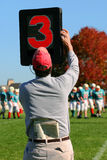 Third Down. Man on sidelines helps mark the downs in a football game Stock Photos