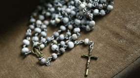Third rosary with crucifix and image of Catholic devotion. Rosary with crucifix and image of Catholic devotion on fabric surface stock photo