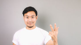 Third step hand sign. An asian man with white t-shirt and grey background stock images