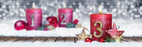 Third sunday of advent red candle with golden metal number one on wooden planks in snow front of silver bokeh background. Third sunday of advent red candle with stock photo