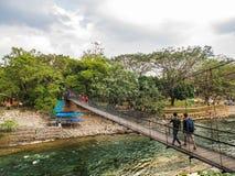 People walking on the suspension bridge in Bohorok River, Bukit Lawang, Indonesia. This is the third suspension bridge can be found in in Bohorok River, Bukit stock photo