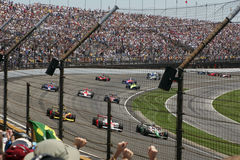 Third Turn. Race cars rounding a turn at the race track, seats filled with cheering fans royalty free stock photo